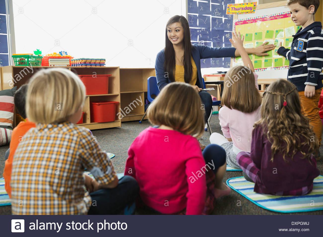 Insegnante rivedendo i giorni della settimana con gli studenti elementari Immagini Stock