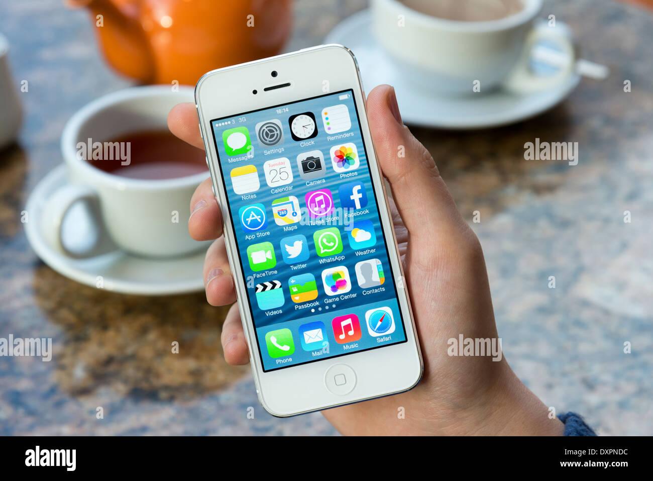 IOS 7 nella schermata iniziale del bianco Apple iPhone 5 in un cafe Immagini Stock