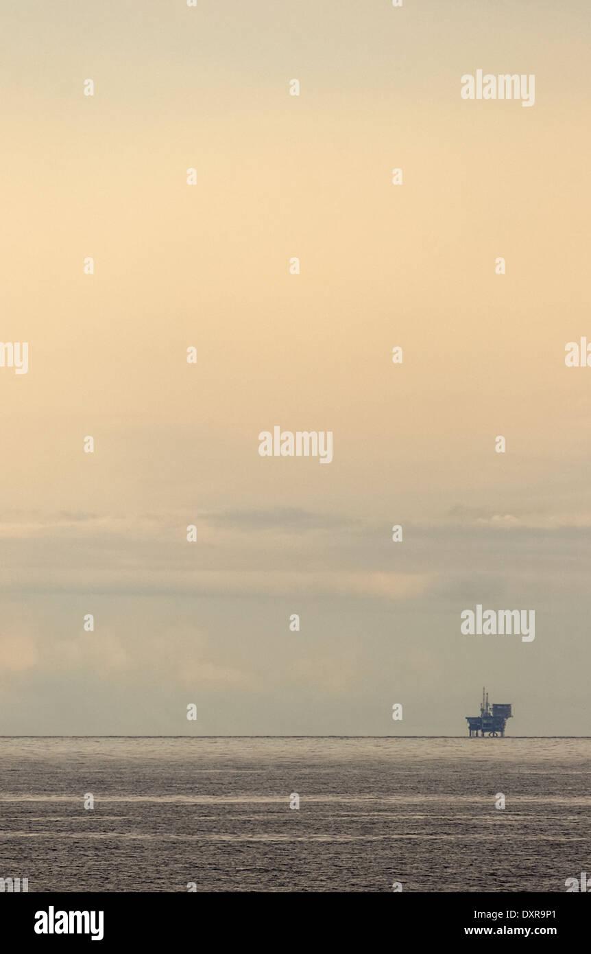 Unico olio/gas rig lontano all'orizzonte contro un vago del cielo della sera. Immagini Stock