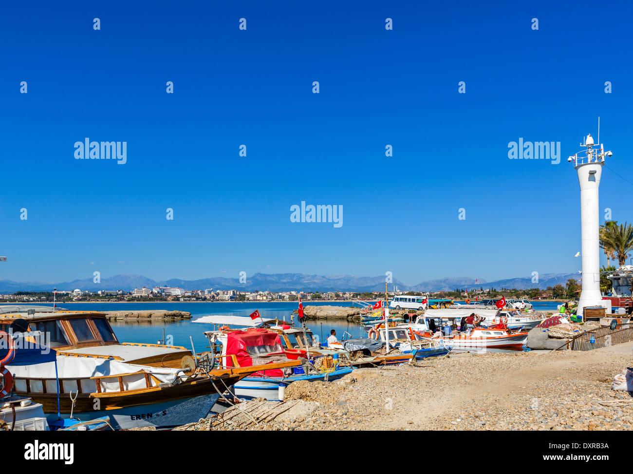 Barche da pesca nella città vecchia porto guardando verso le spiagge e hotel zona ad ovest della città, laterale, Provincia di Antalya, Turchia Foto Stock