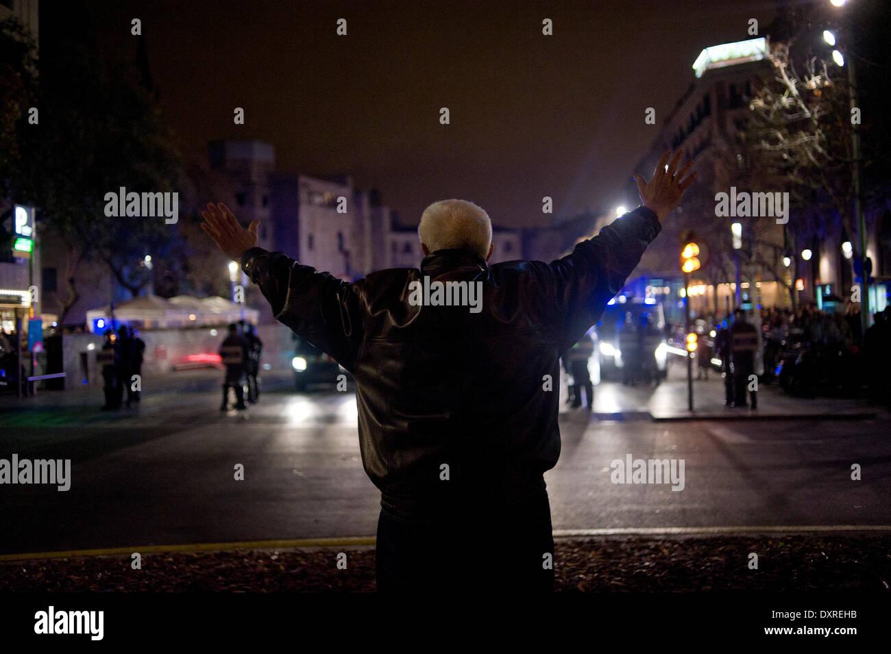 Barcellona, Spagna -29th marzo, 2014. Un manifestante con le braccia aperte in atteggiamento pacifista verso una sommossa cordone di polizia. Una manifestazione svoltasi a Barcellona da diversi gruppi sociali contro i tagli e la repressione si è conclusa con scontri con la polizia nel centro della citta'. Credito: Jordi Boixareu/Alamy Live News Immagini Stock