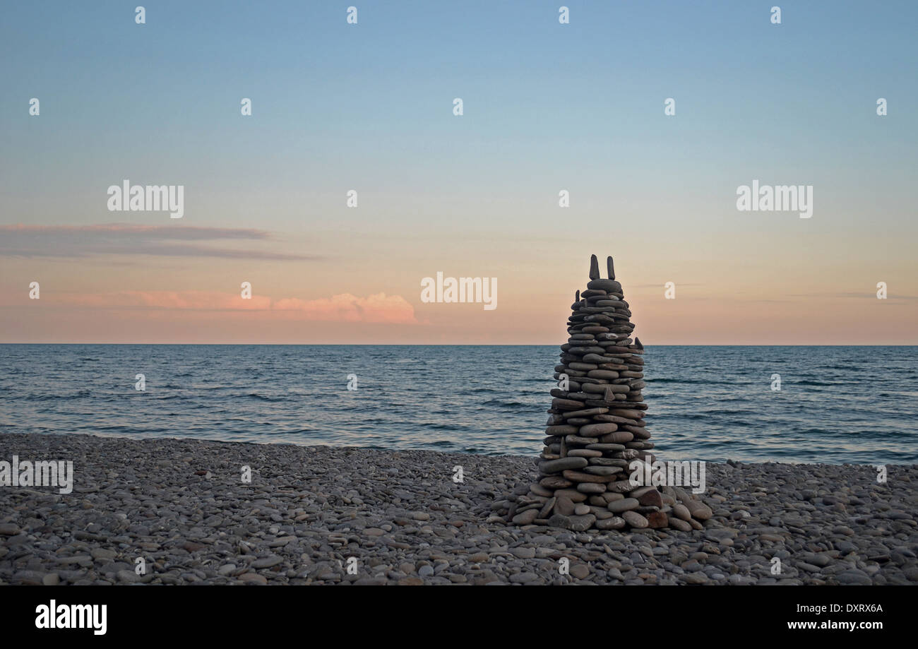 La piramide di pietre sulla spiaggia durante il tramonto Immagini Stock