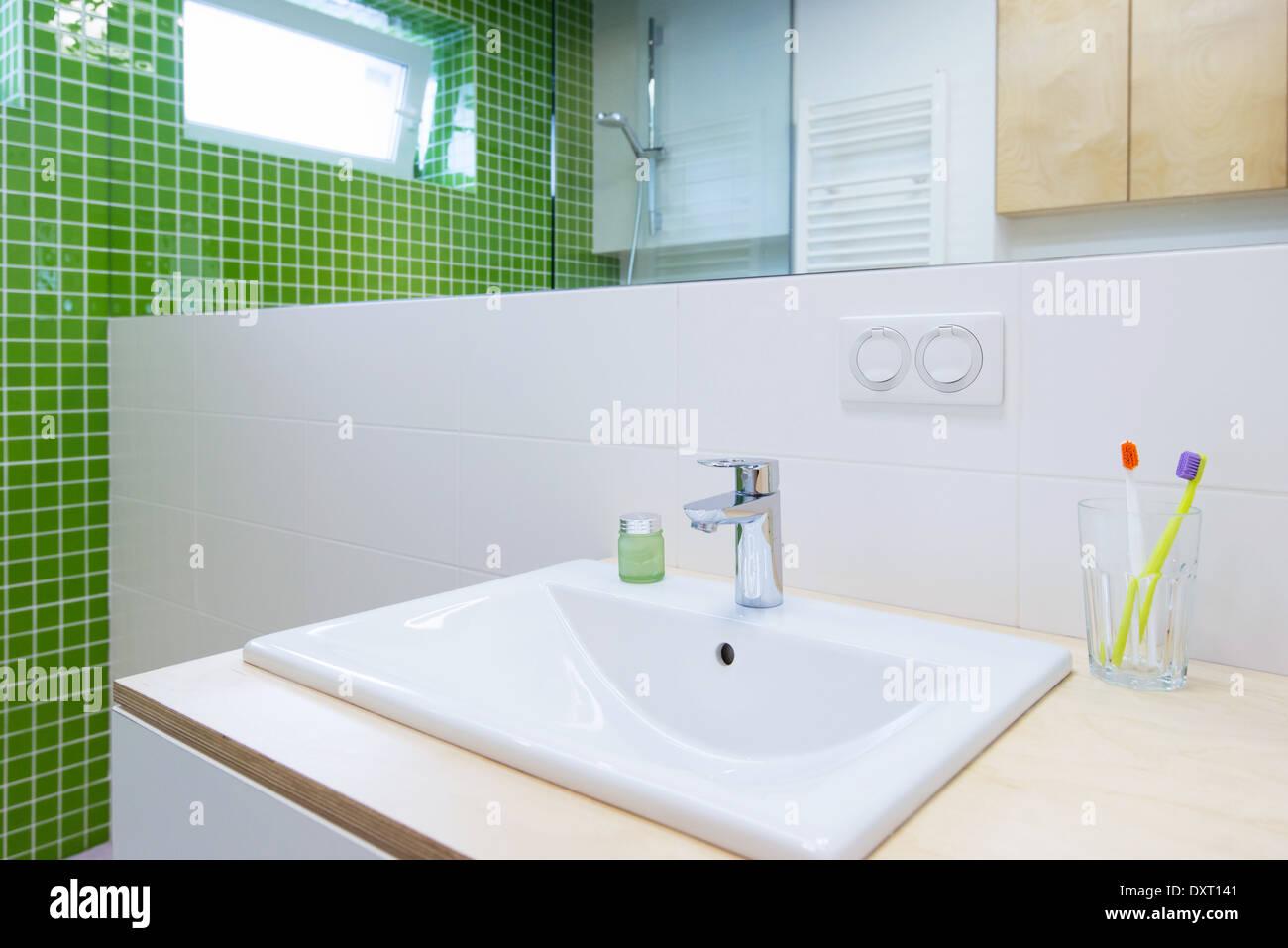 Lavandino con rubinetto nel bagno di colore verde foto immagine