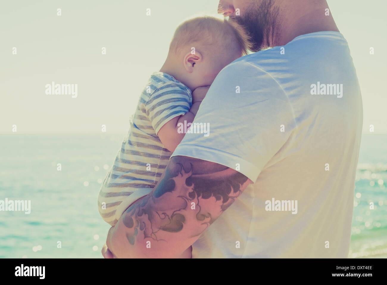 Close up di padre holding baby figlio presso la spiaggia Immagini Stock