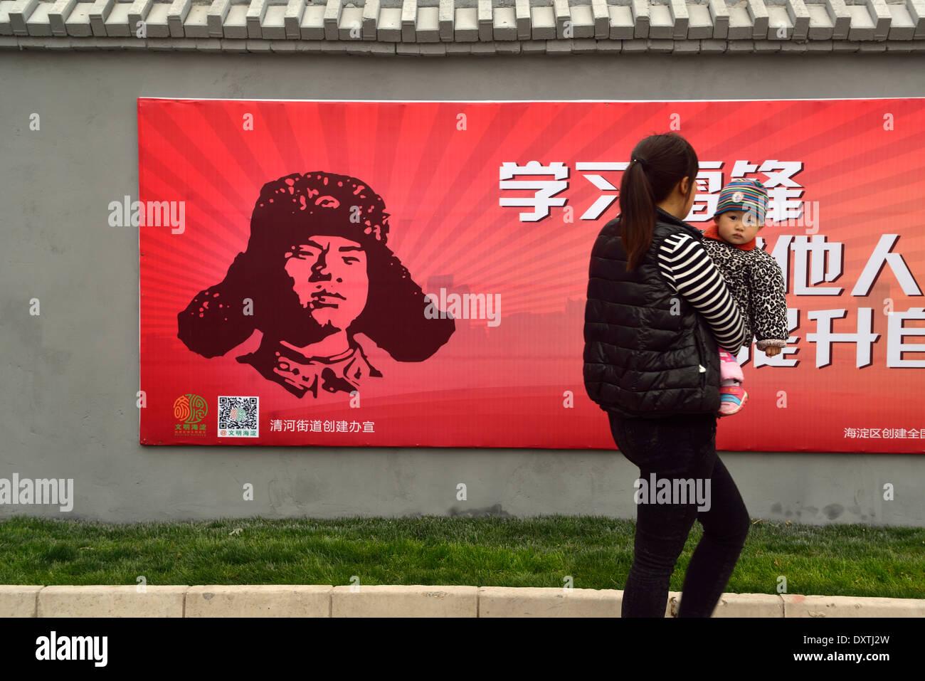 Una madre cinese detiene un bambino passato un cartellone con Lei Feng a Pechino in Cina. 27-Mar-2014 Immagini Stock