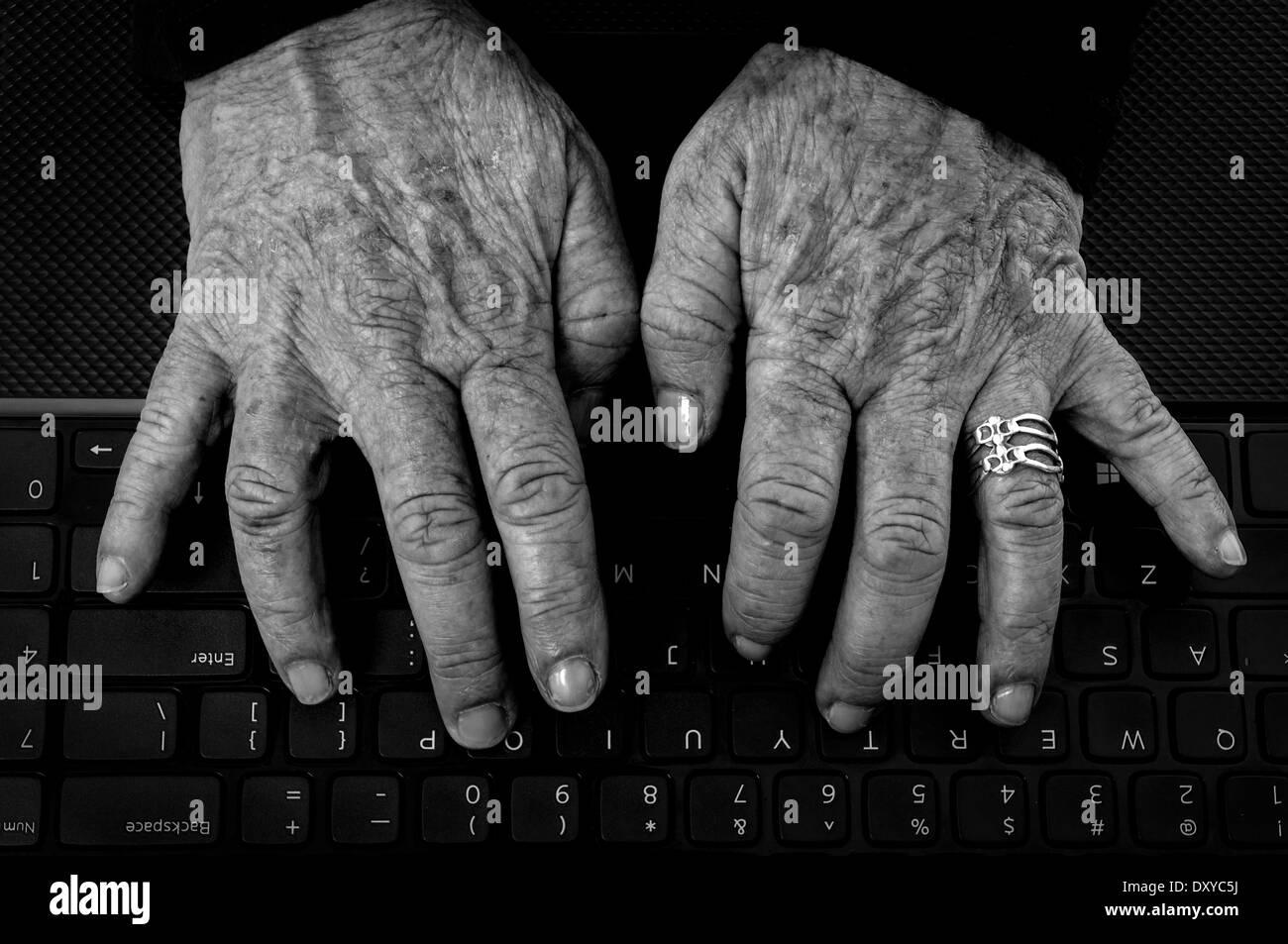 Primo piano della vecchia donna con le mani Artrite su una tastiera di computer in bianco e nero Immagini Stock