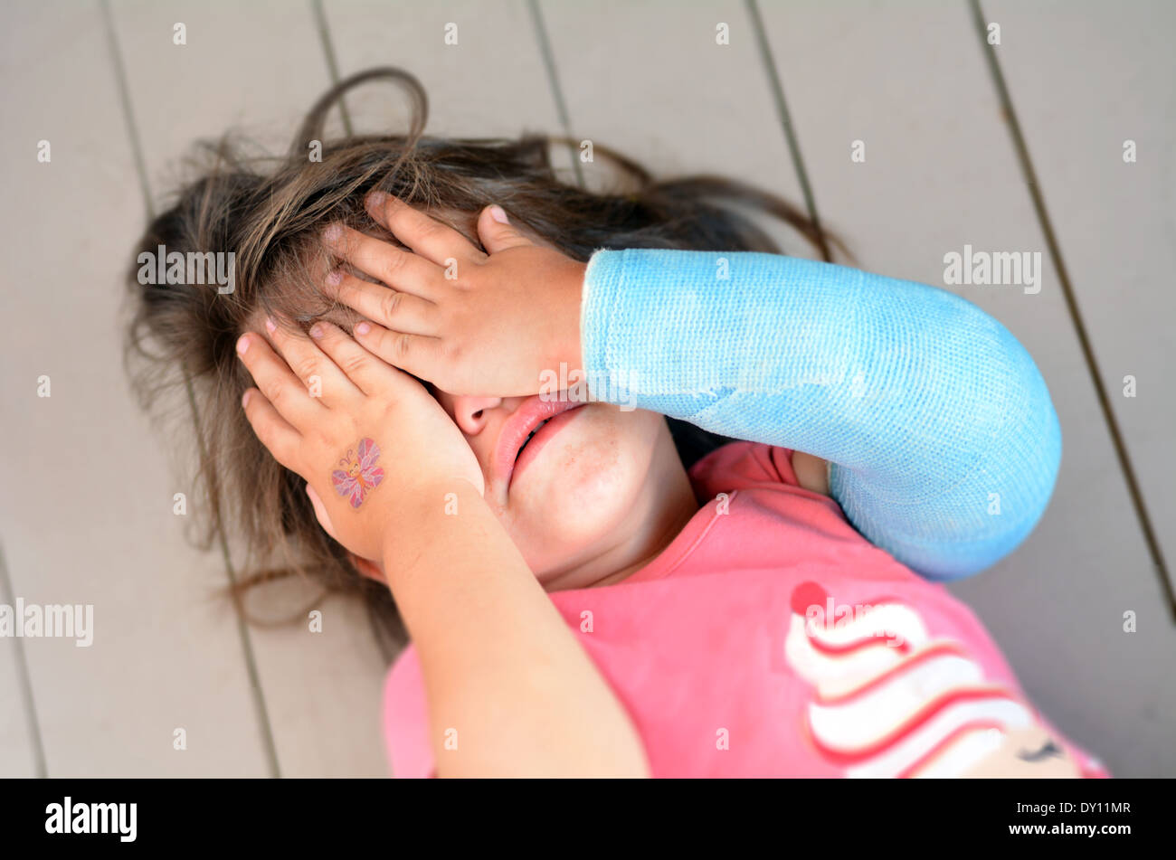 Abusato della bambina con un braccio rotto che copre la faccia qui durante il pianto. Concetto foto di abusi nei confronti dei bambini, violenza domestica Immagini Stock