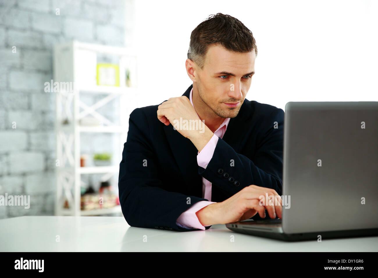 Fiducioso imprenditore lavora su un computer portatile in ufficio Immagini Stock