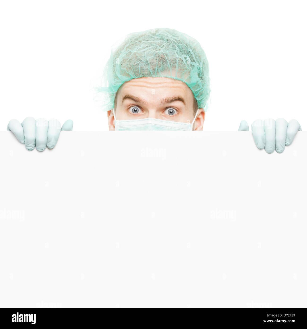 Chirurgo guardando da dietro un pannello isolato su sfondo bianco Immagini Stock