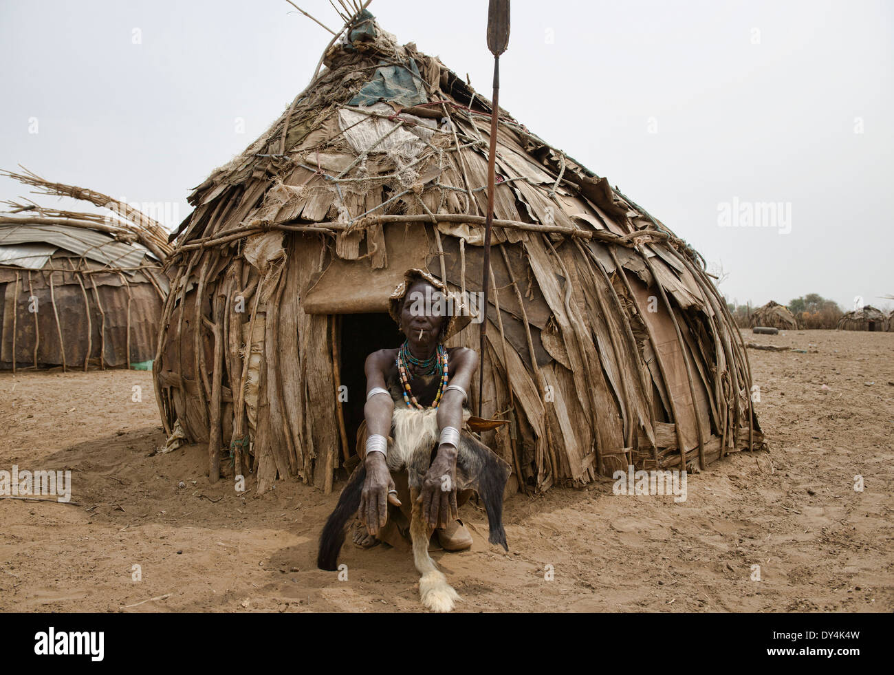 Vecchia donna Dassanech nella parte anteriore del suo rifugio nella bassa valle dell'Omo di Etiopia Immagini Stock