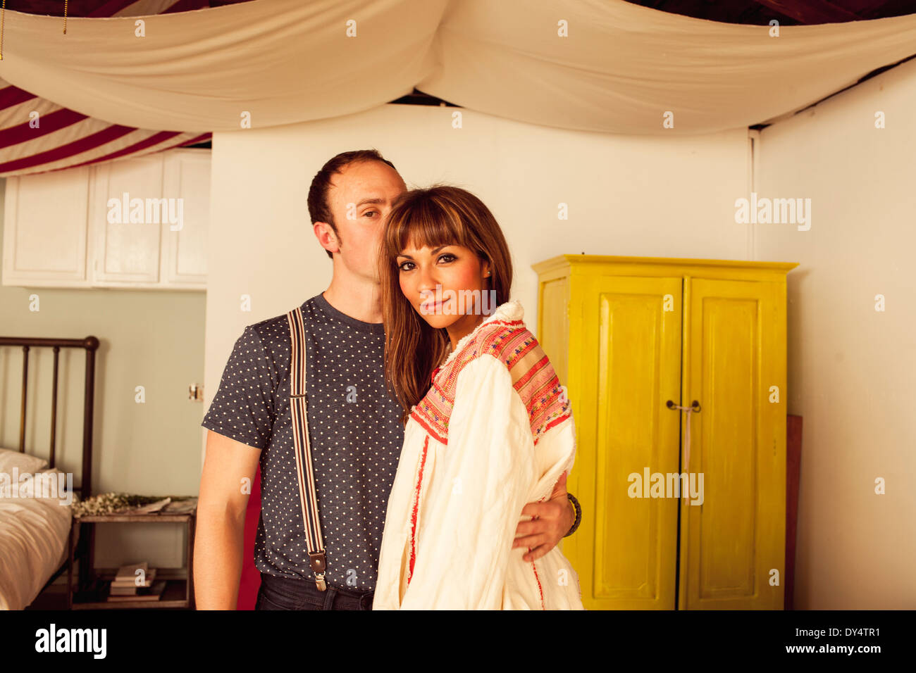 Uomo con braccio attorno alla donna in camera da letto Immagini Stock