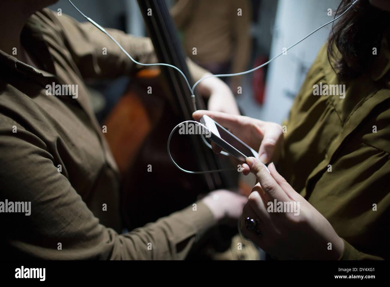 La sezione centrale dei giovani per ascoltare musica sullo smartphone Immagini Stock