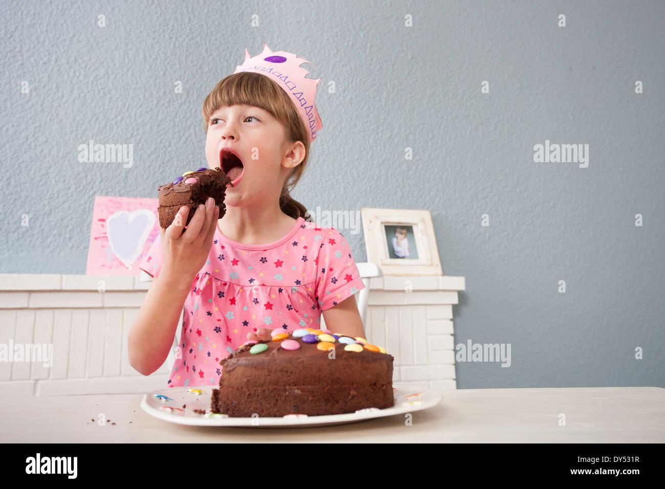 Ragazza di mangiare la sua torta di compleanno Immagini Stock