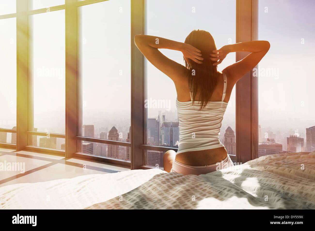 Giovane donna seduta sul letto, stretching, affacciato sulla città Immagini Stock
