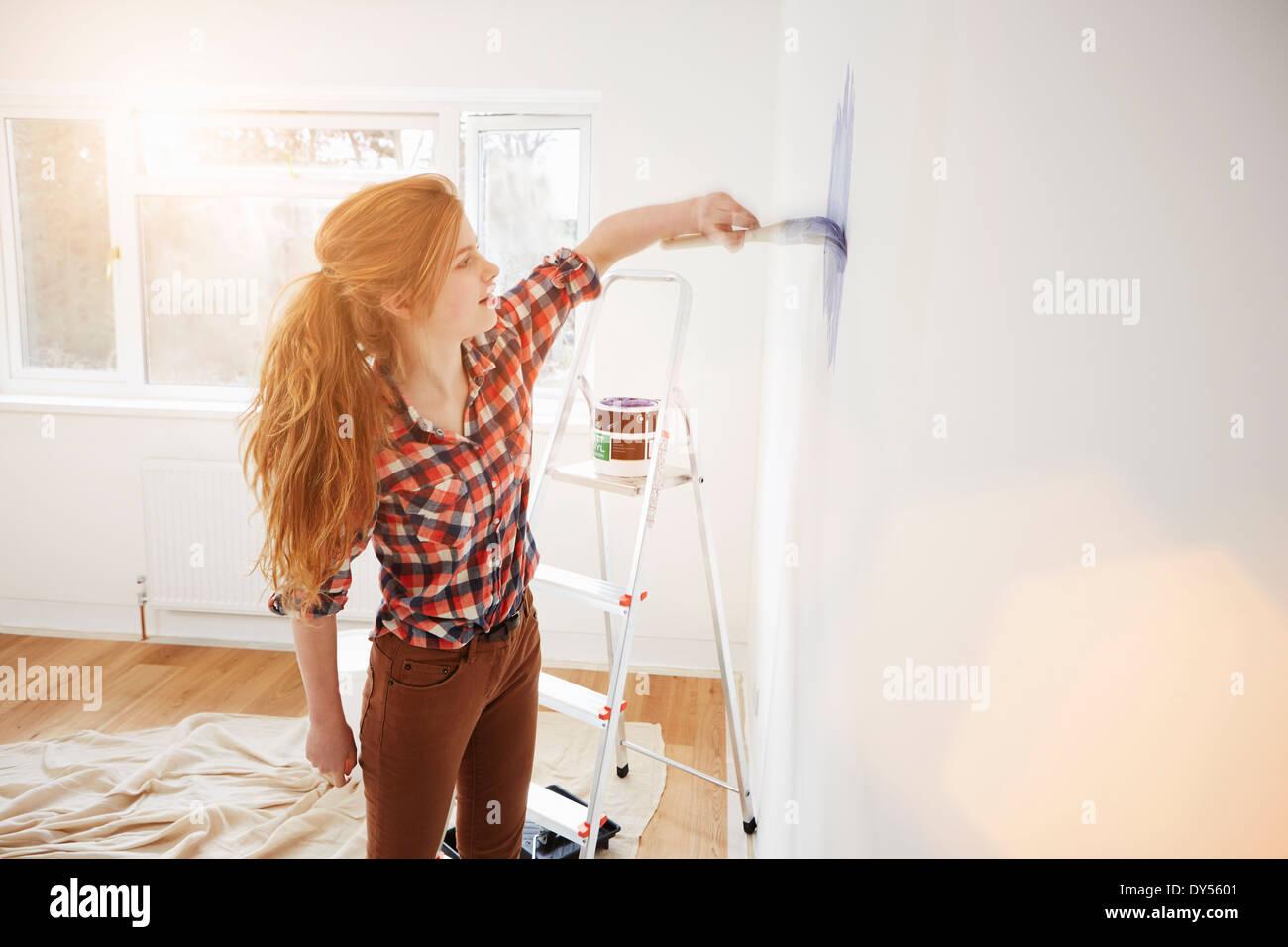 Ragazza adolescente pittura la sua camera da letto parete Immagini Stock