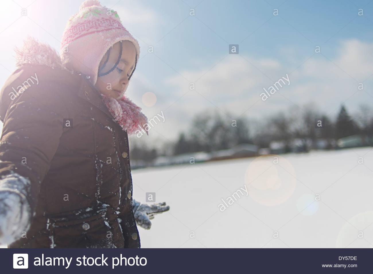 Ragazza giovane con cautela cercando di camminare nella neve campo coperto Immagini Stock