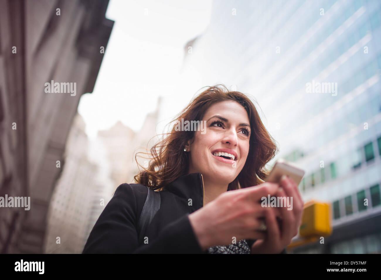 Giovane donna tenendo il telefono cellulare, New York, Stati Uniti d'America Immagini Stock