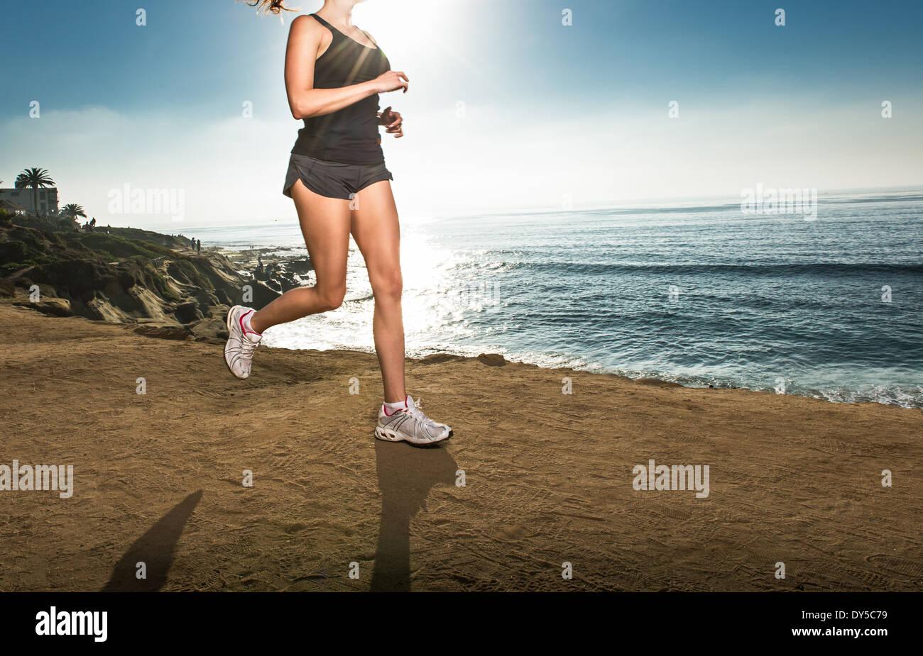 Metà donna adulta jogging lungo la scogliera Immagini Stock