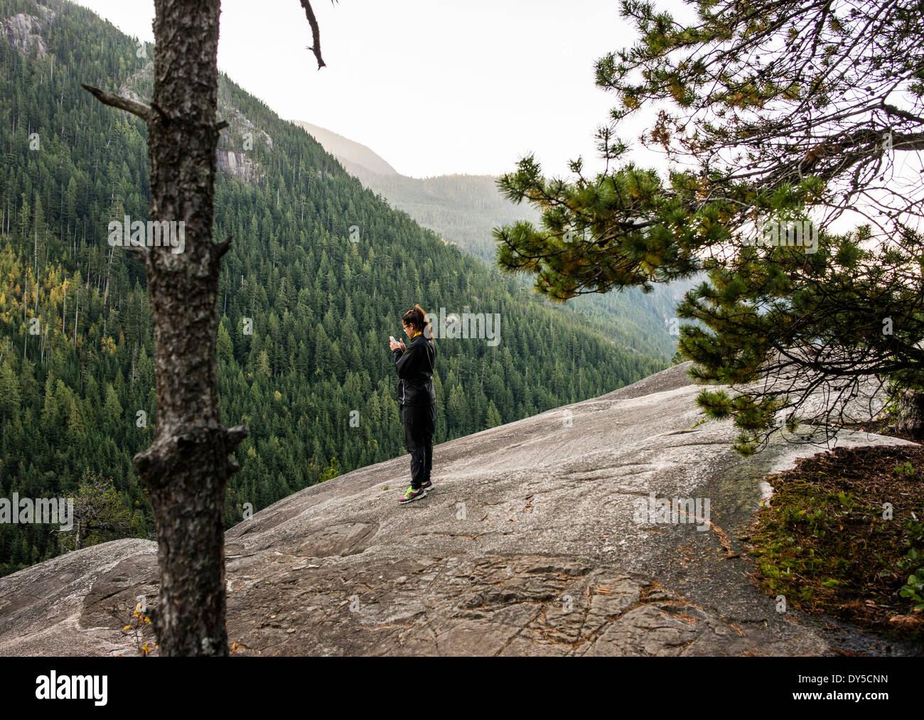 Giovane donna guardando smartphone, Squamish, British Columbia, Canada Immagini Stock