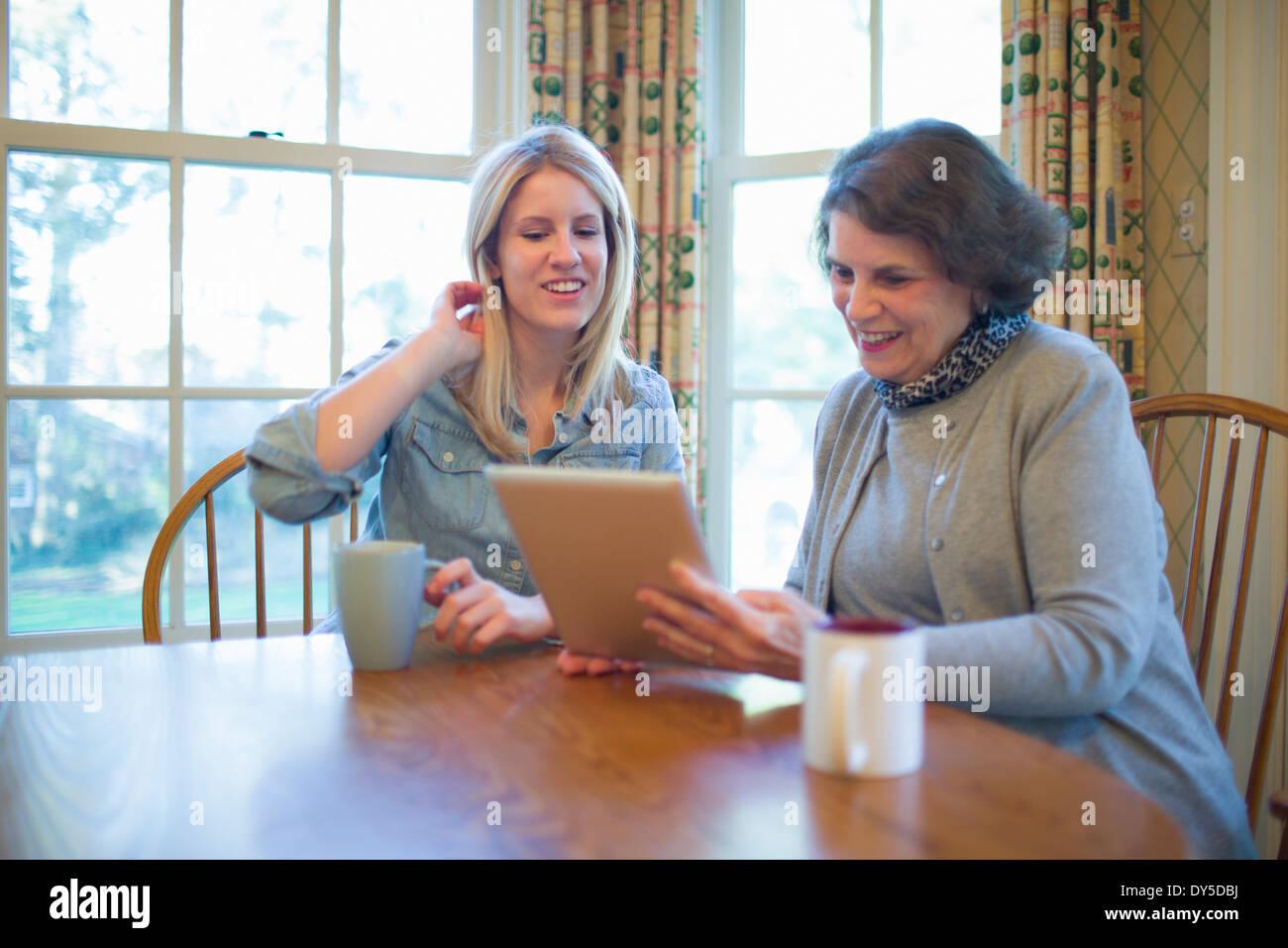 Donna Senior e nipote guardando a tavoletta digitale Immagini Stock