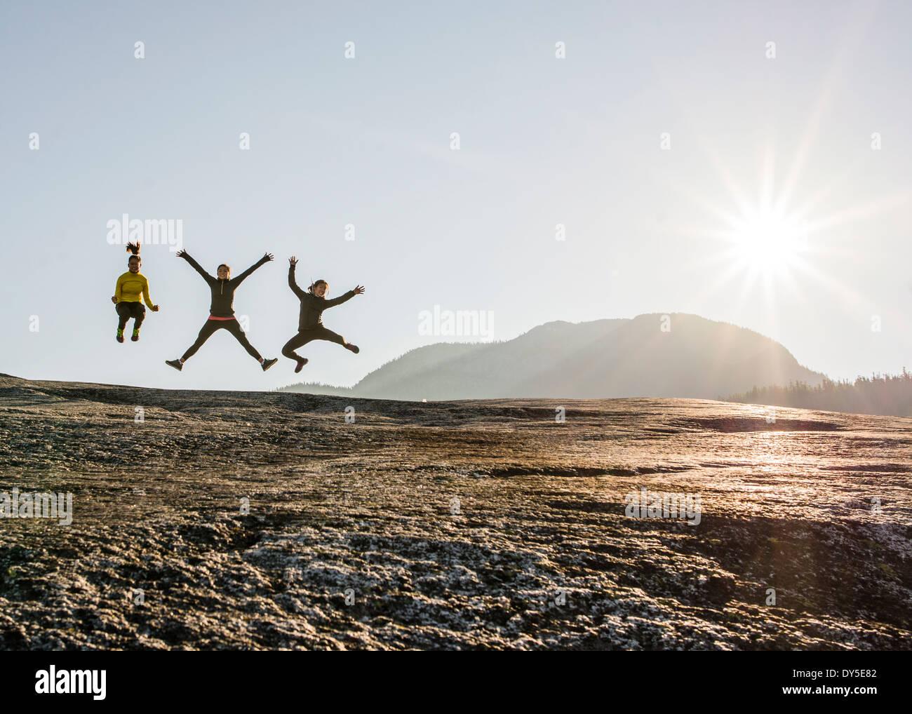 Tre giovani femmine escursionisti jumping mezza aria su roccia, Squamish, British Columbia, Canada Immagini Stock