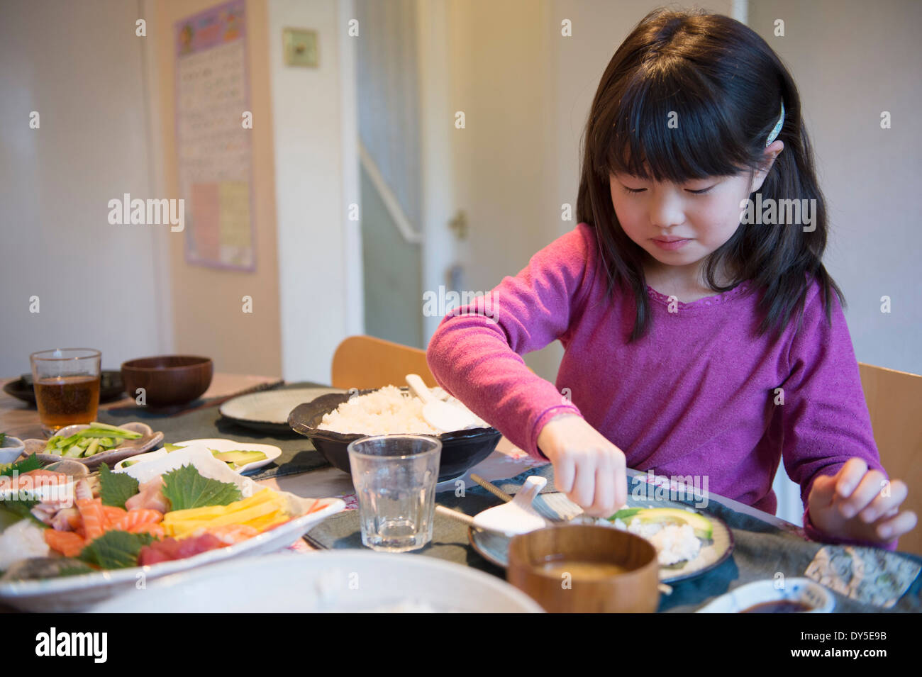 Ragazza la selezione di pasti da piatti sul tavolo da pranzo Immagini Stock