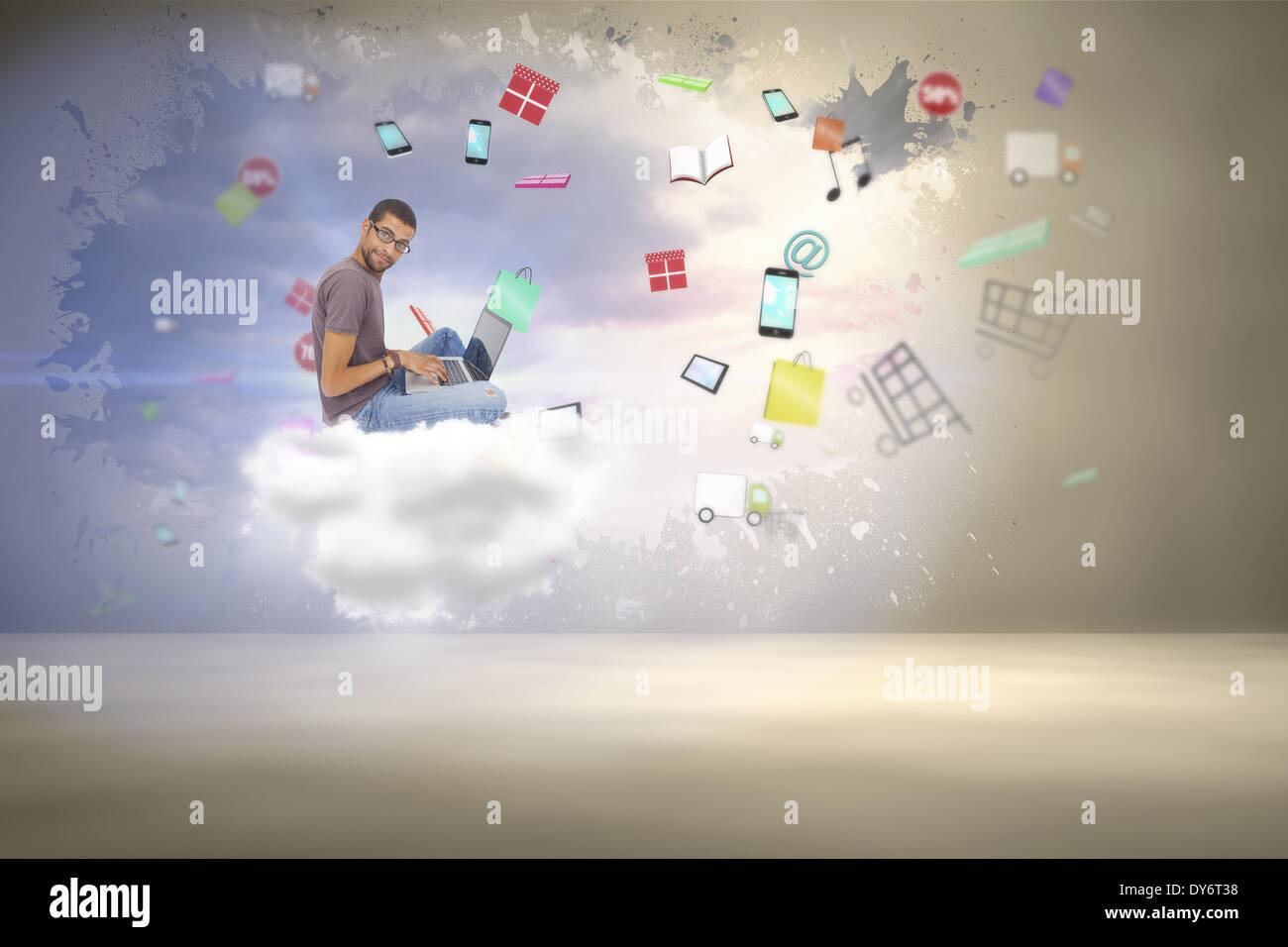 Immagine composita dell'uomo con gli occhiali seduto sul pavimento con il laptop e guardando la fotocamera Immagini Stock
