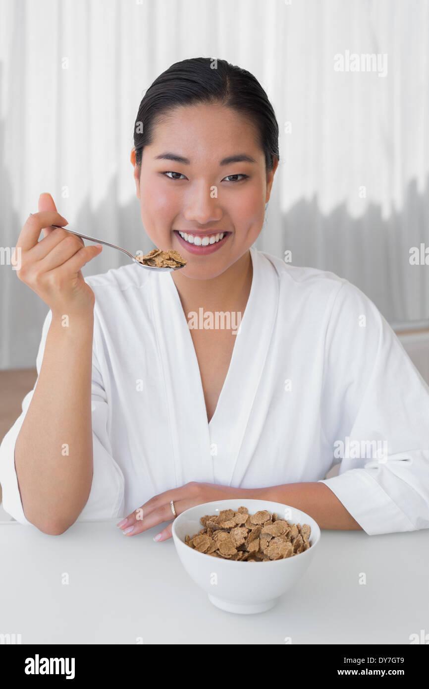 Donna felice in accappatoio avente la sua prima colazione Immagini Stock