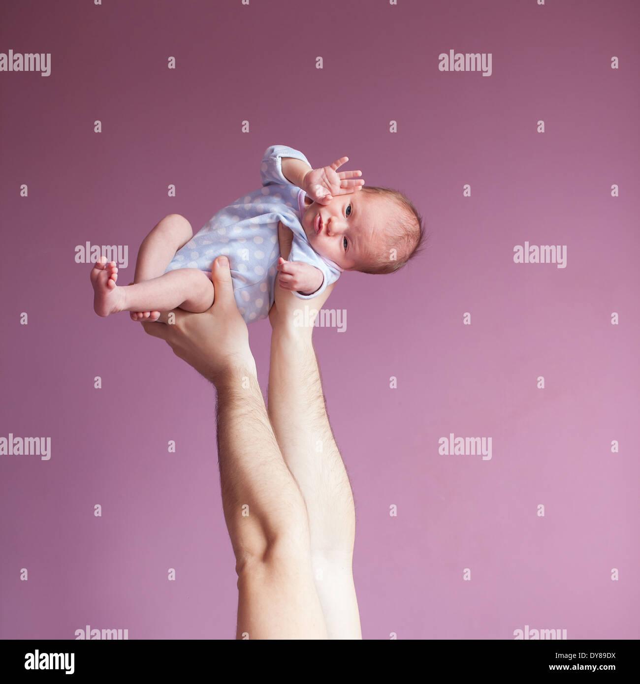 Ciao, mondo! Padre tenendo le mani a due settimana neonato Immagini Stock