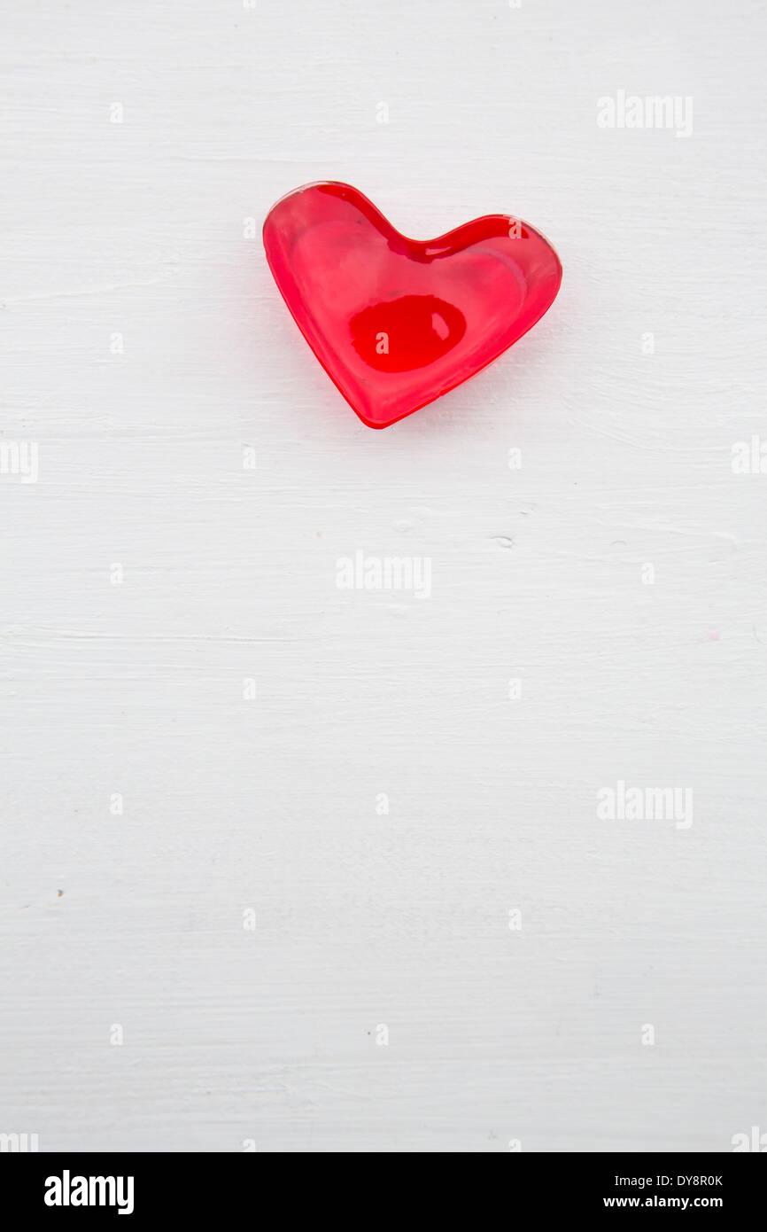 Rosso a forma di cuore di gelatina di ciliegia sulla terra bianca Immagini Stock