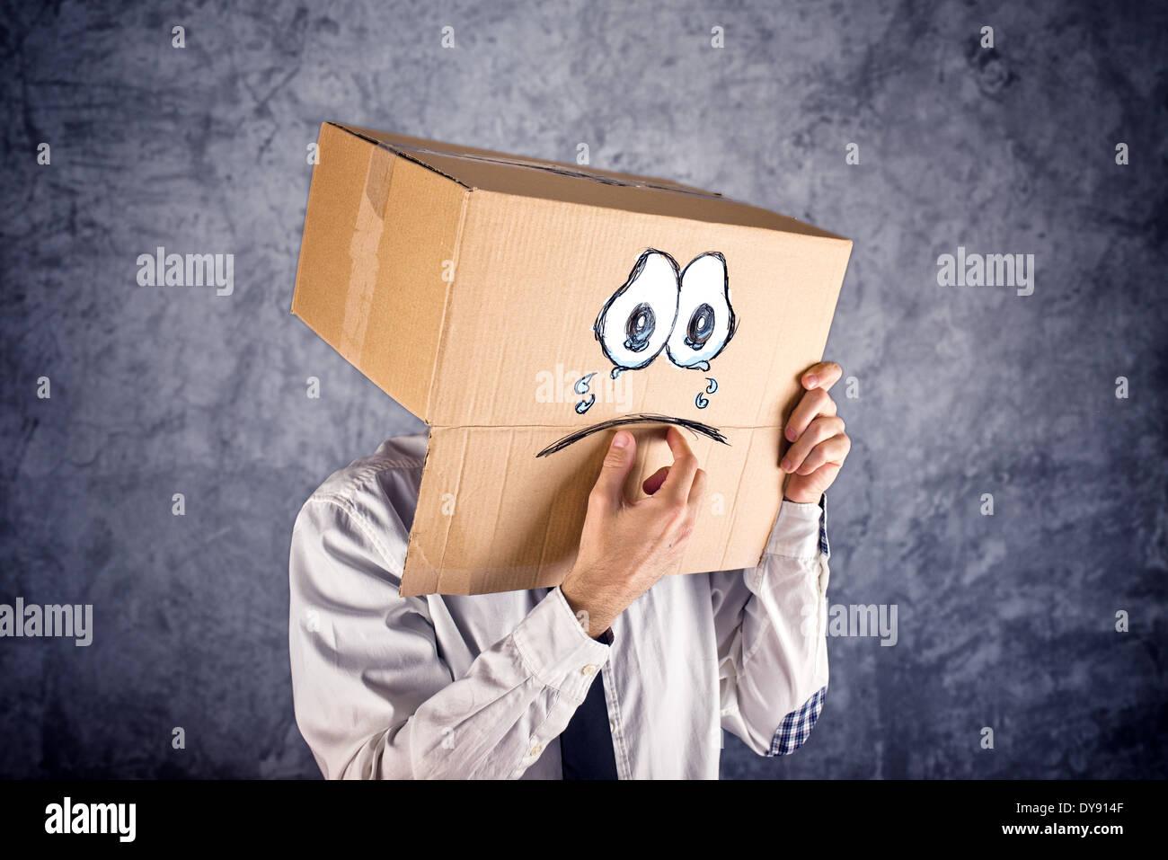 Imprenditore con scatola di cartone sulla sua testa e tristi lacrime di espressione. Concetto di tristezza e depressione. Immagini Stock