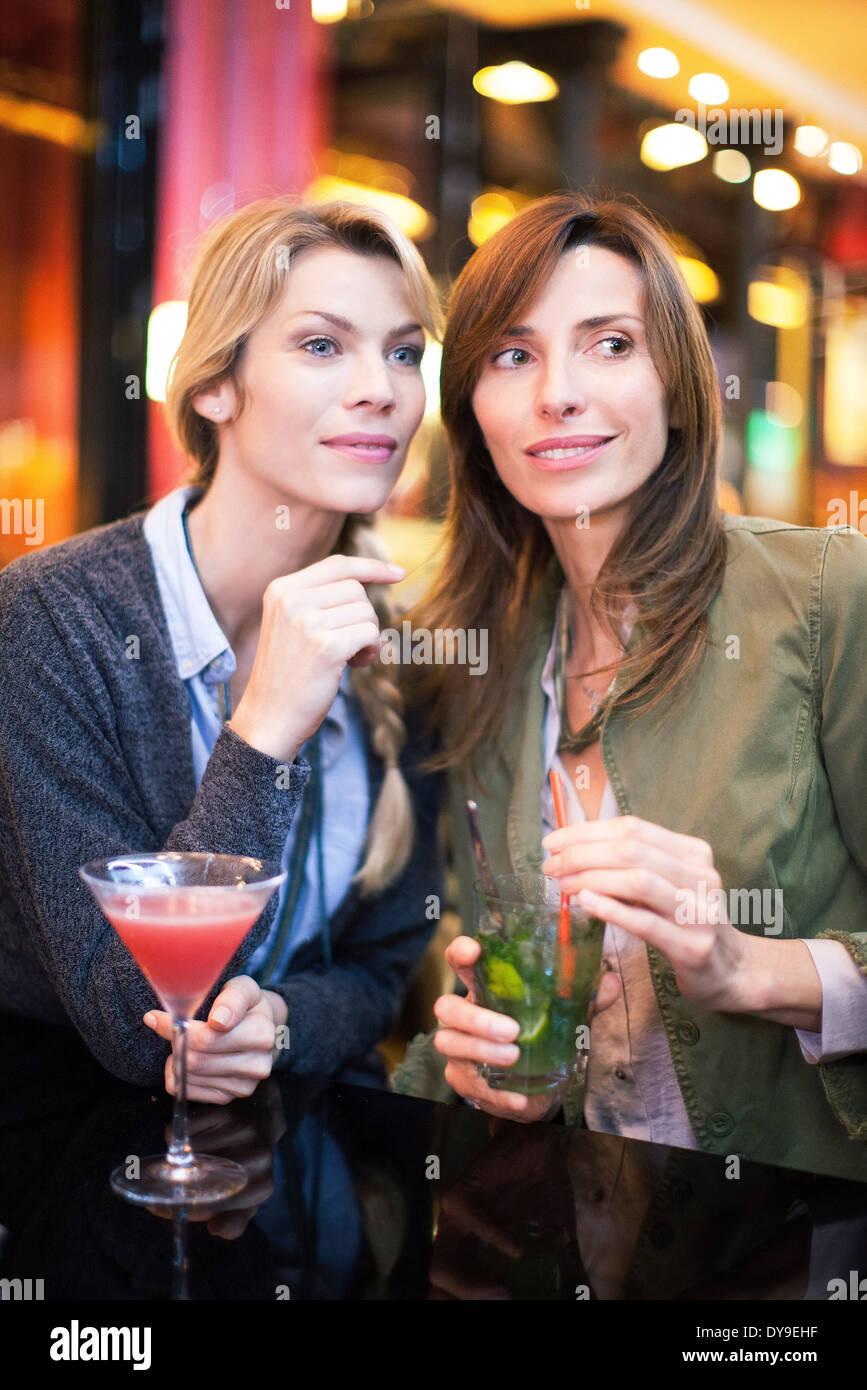Le donne aventi un cocktail presso il bar Immagini Stock
