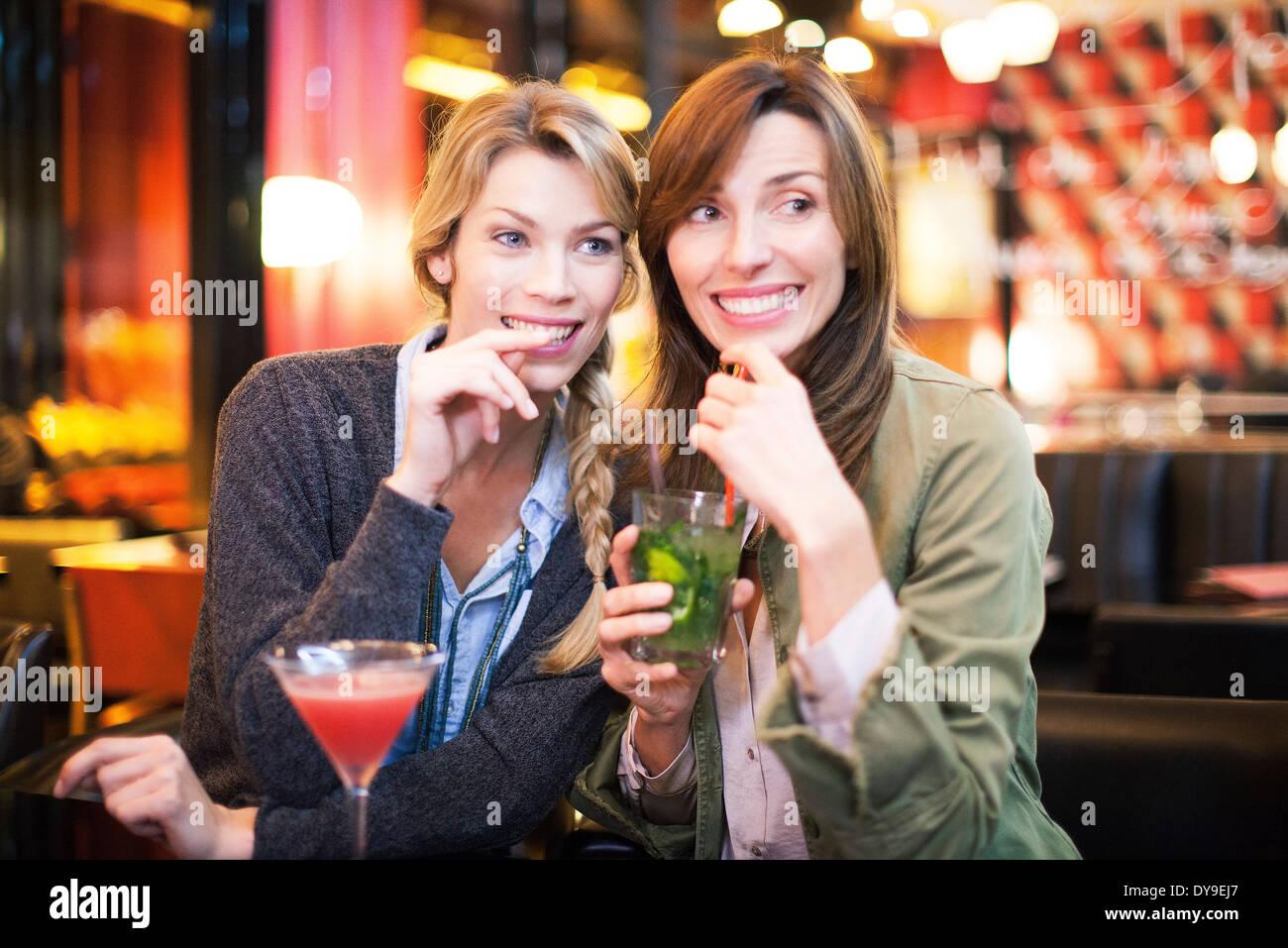 Le donne aventi un cocktail nel bar Immagini Stock