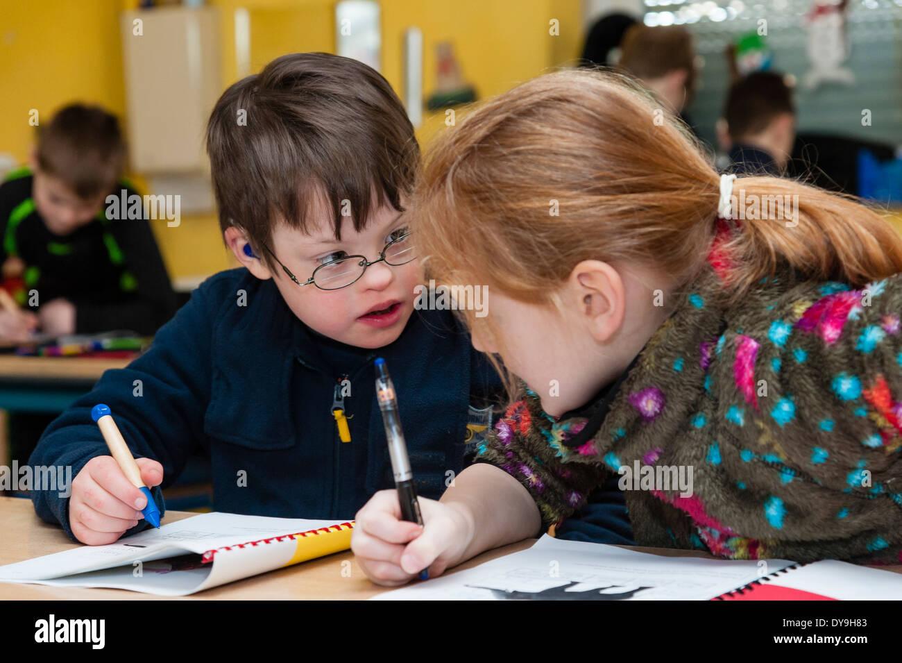 Non-disabili e gli alunni disabili (in questo caso un ragazzo che soffre di sindrome di Down) imparare insieme nella stessa classe. Immagini Stock