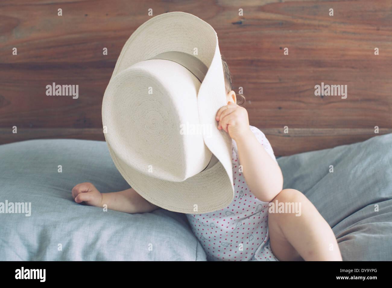Il bambino con la faccia oscurata da oversized hat Immagini Stock