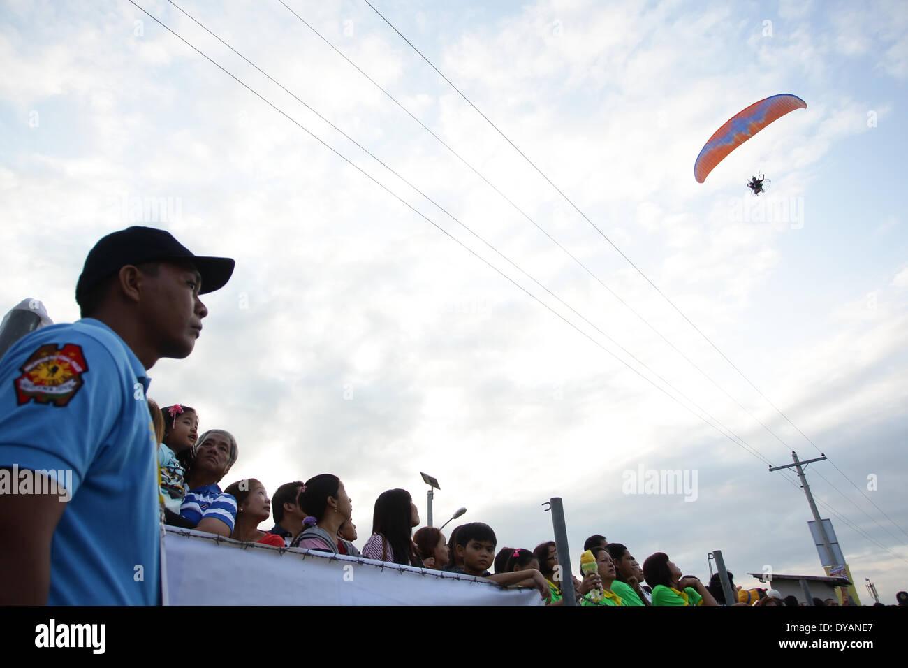 Lubao, Pampanga, Filippine. Xi Apr, 2014. La gente guarda un paramotore passano al Philippine International Hot Air Balloon Festival on April 11, 2014. Il Philippine International Mongolfiera Festival featured 21 paesi con 37 palloncini. Credito: Mark Cristino/NurPhoto/ZUMAPRESS.com/Alamy Live News Immagini Stock