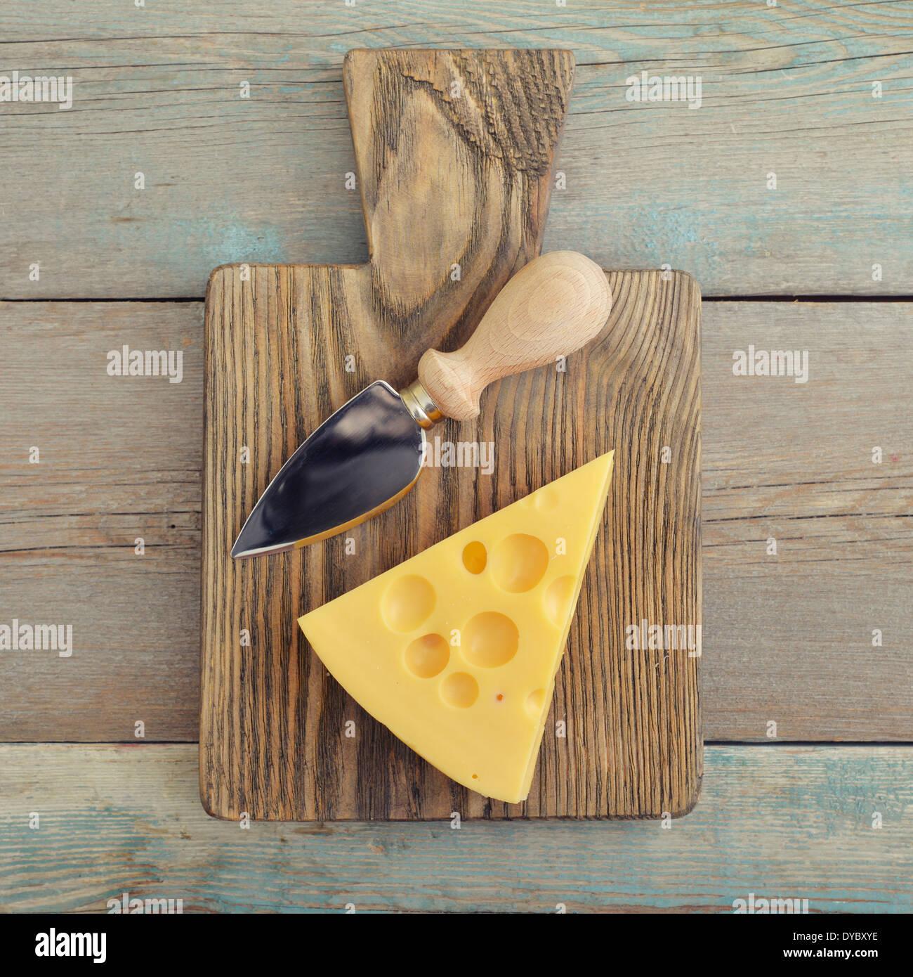 Formaggio con grandi fori e il coltello sul tagliere di legno Immagini Stock