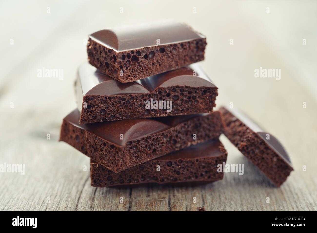 Cioccolato poroso in pila su un sfondo di legno closeup Immagini Stock