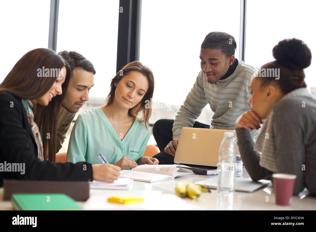 Diversi gruppi di giovani studenti di lavorare insieme su scuola assegnazioni. Popolazione multietnica studiando insieme a una tabella. Immagini Stock