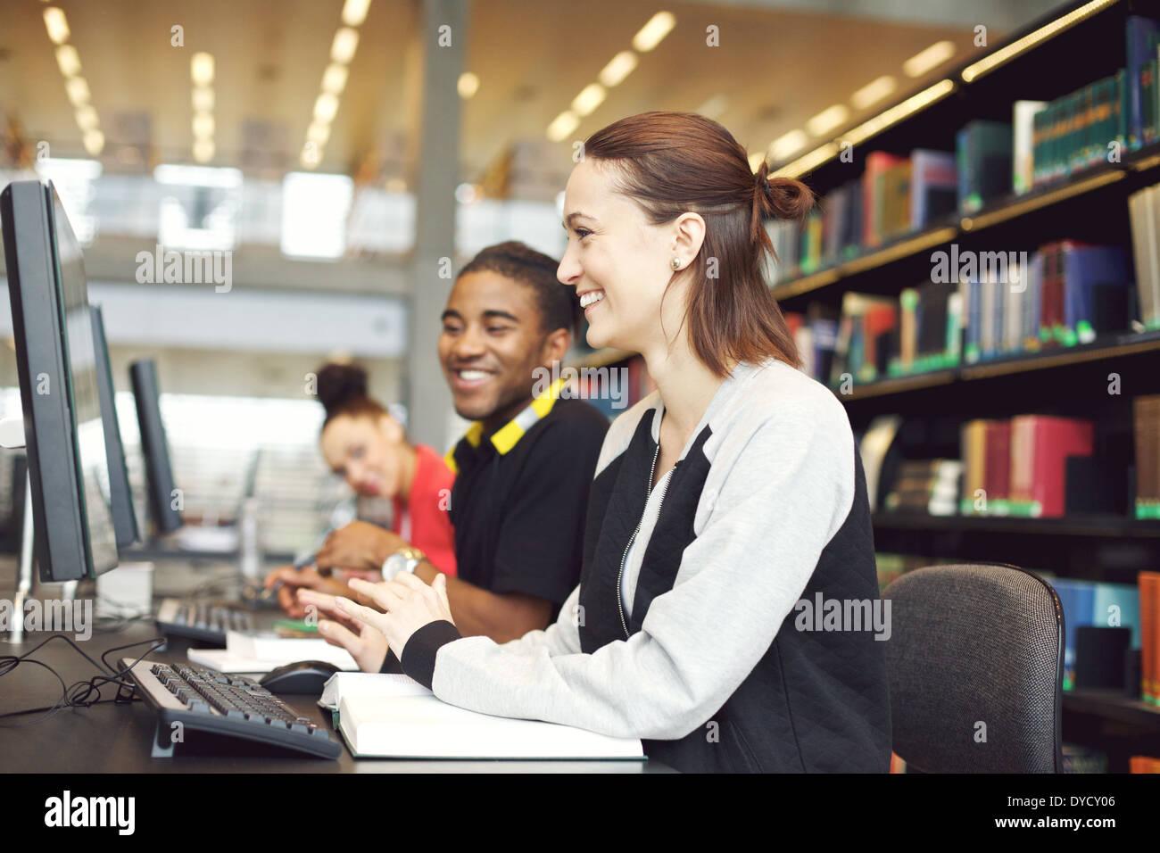 Multietnica gli studenti seduti al tavolo utilizzando il computer per la ricerca di informazioni per il loro studio. I giovani studenti universitari. Immagini Stock