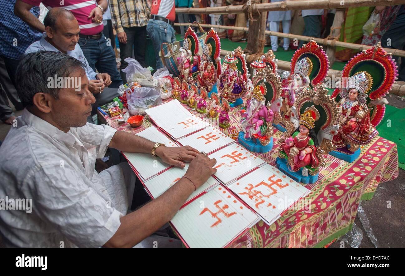 Calcutta, lo stato indiano del Bengala Occidentale. 15 apr 2014. Un sacerdote indiano dipinge i santi segni sulla prima pagina del nuovo libro mastro della contabilità libri nella parte anteriore del Signore Ganesha e la dea Lakshmi a Calcutta, capitale dell'est lo stato indiano del Bengala Occidentale, 15 aprile 2014. Poila Baishakh, il primo giorno del calendario Bengali anno, è l'inizio di tutte le attività aziendali nel Bengala occidentale quando i commercianti culto del Signore Ganesha e la dea Lakshmi per contrassegnare l'anno con la ricchezza e la prosperità. © Tumpa Mondal/Xinhua/Alamy Live News Immagini Stock
