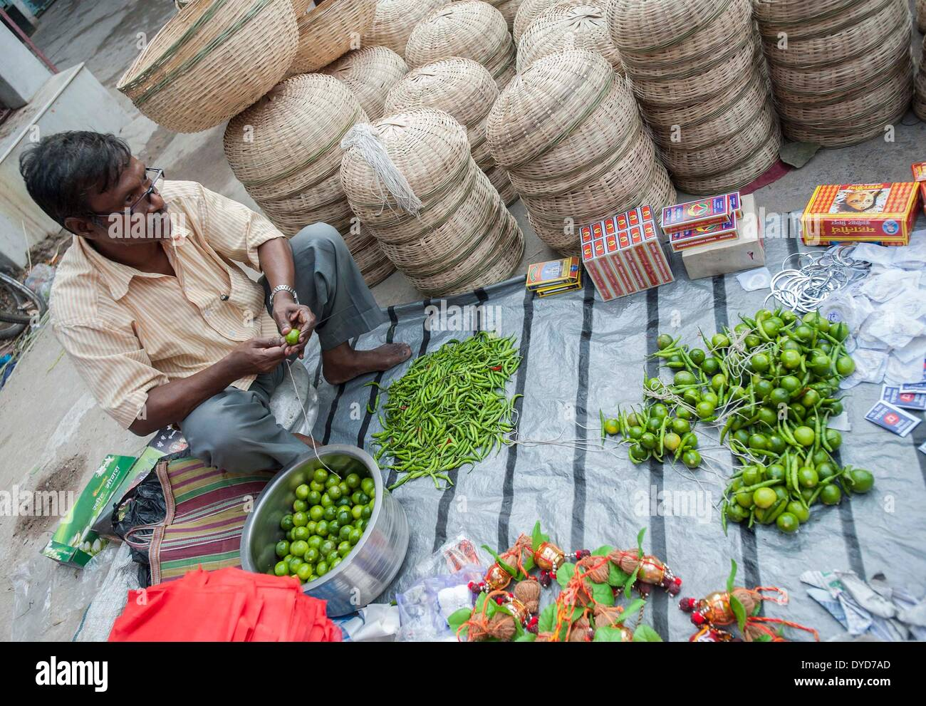 Calcutta, lo stato indiano del Bengala Occidentale. 15 apr 2014. Un indiano hawker rende stringhe di limone e peperoncino come proprietari di negozi appendiabiti a loro come portafortuna a Calcutta, capitale dell'est lo stato indiano del Bengala Occidentale, 15 aprile 2014. Poila Baishakh, il primo giorno del calendario Bengali anno, è l'inizio di tutte le attività aziendali nel Bengala occidentale quando i commercianti culto del Signore Ganesha e la dea Lakshmi per contrassegnare l'anno con la ricchezza e la prosperità. © Tumpa Mondal/Xinhua/Alamy Live News Immagini Stock