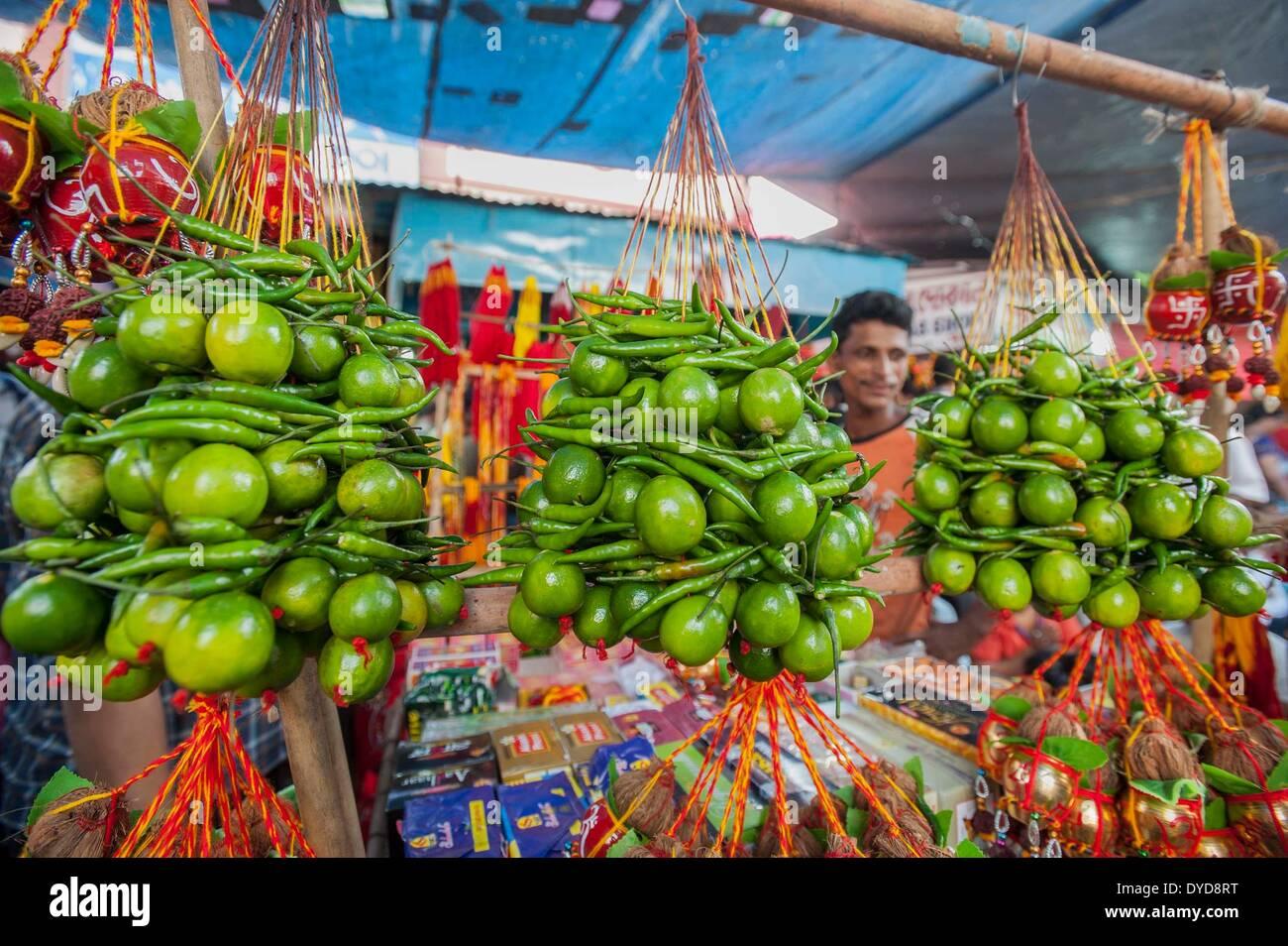 Calcutta, lo stato indiano del Bengala Occidentale. 15 apr 2014. Stringhe di limoni e peperoncini rossi sono venduti come proprietari di negozi appendiabiti a loro come portafortuna su 'Poila Baishakh' in Calcutta, capitale dell'est lo stato indiano del Bengala Occidentale, 15 aprile 2014. Poila Baishakh, il primo giorno del calendario Bengali anno, è l'inizio di tutte le attività aziendali nel Bengala occidentale quando i commercianti culto del Signore Ganesha e la dea Lakshmi per contrassegnare l'anno con la ricchezza e la prosperità. © Tumpa Mondal/Xinhua/Alamy Live News Immagini Stock