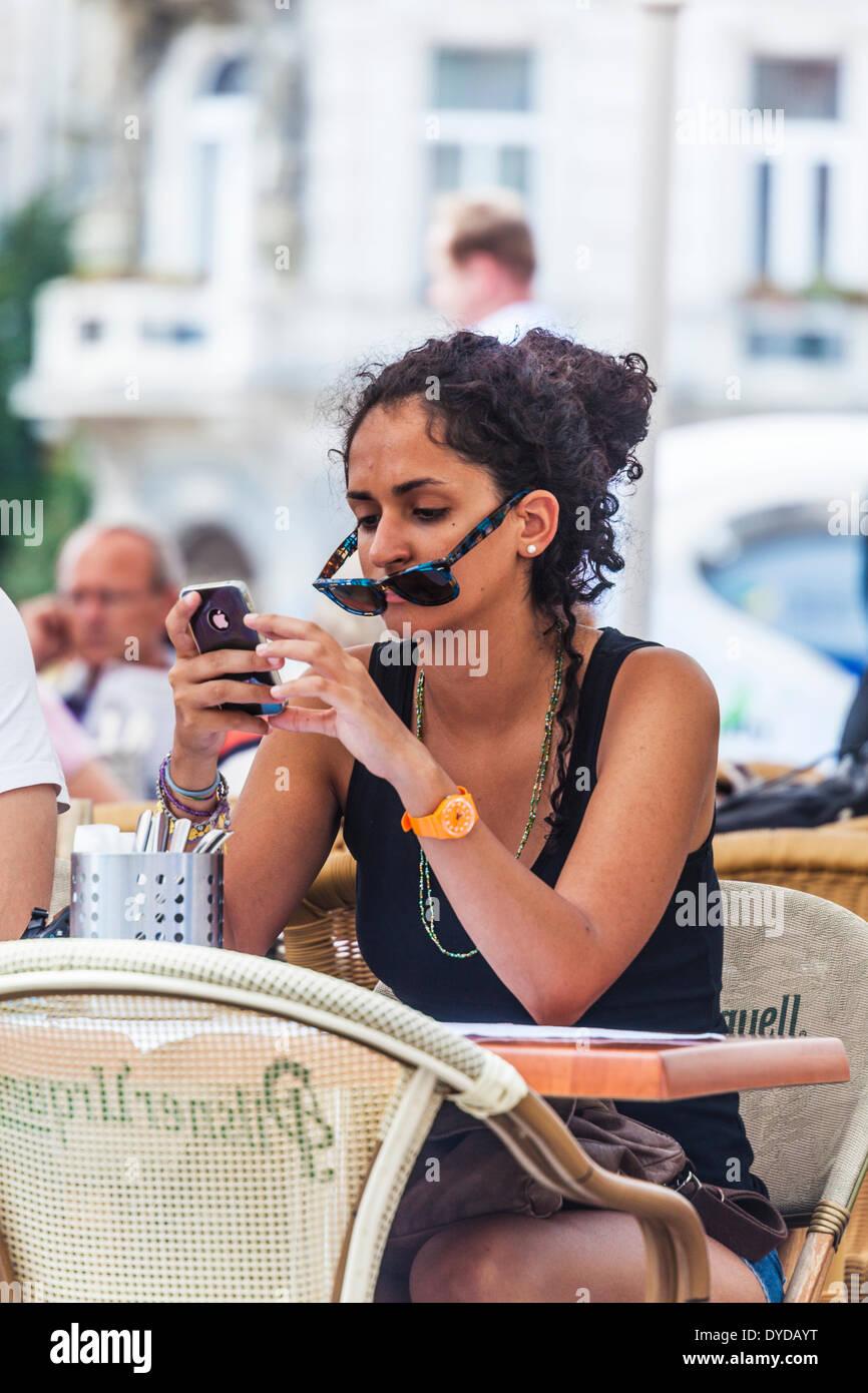 Una giovane donna utilizza il suo iPhone mentre è seduto in un cafe' all'aperto in Piazza della Città Vecchia di Praga. Immagini Stock