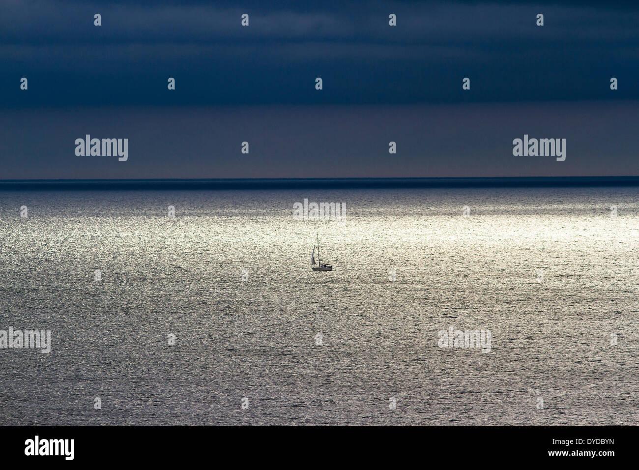 Un piccolo yacht a vela lontano fuori in mare. Immagini Stock