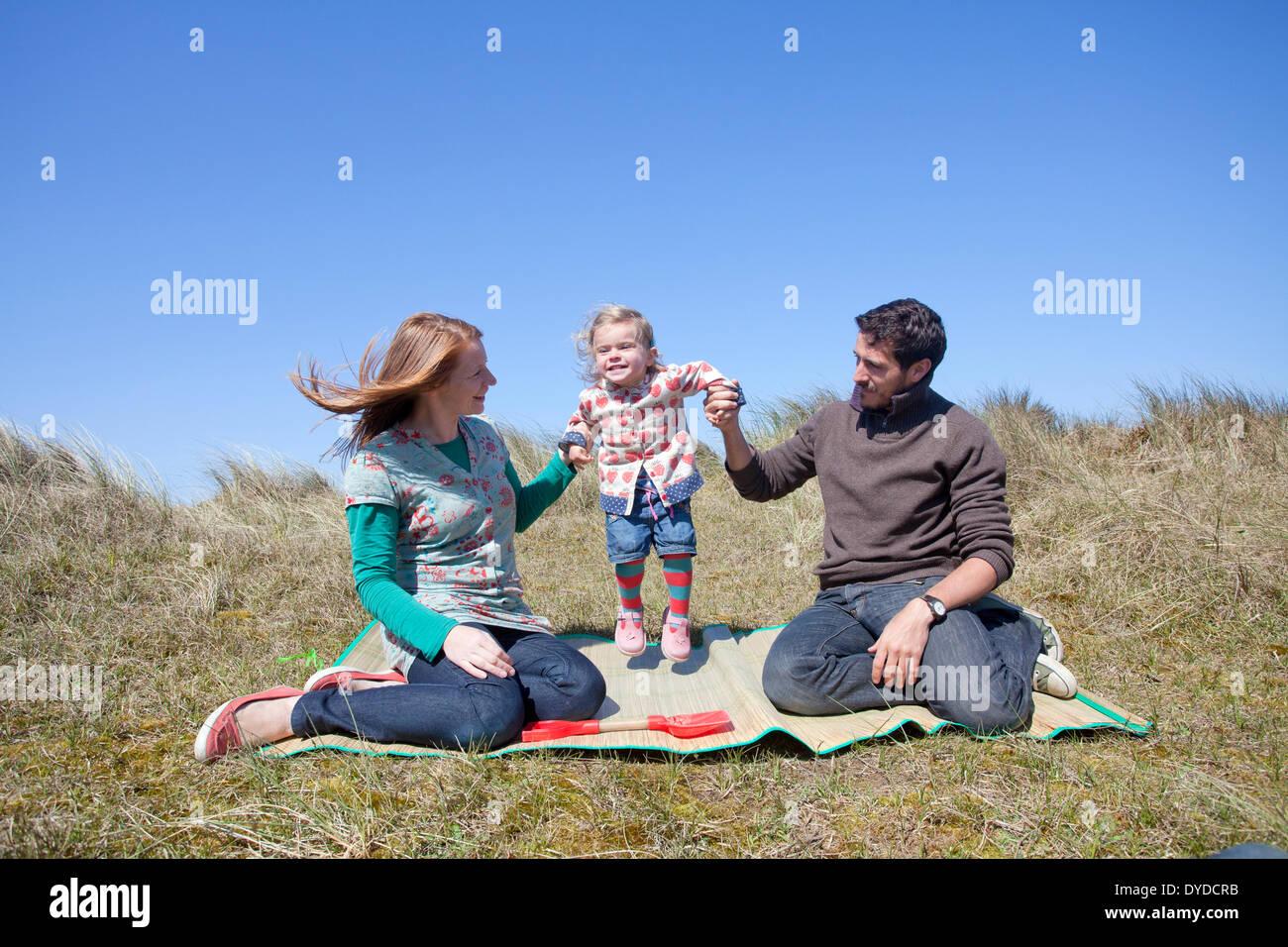 Una giovane famiglia avente il divertimento sulle dune di sabbia a Horsey spiaggia sulla costa di Norfolk. Foto Stock