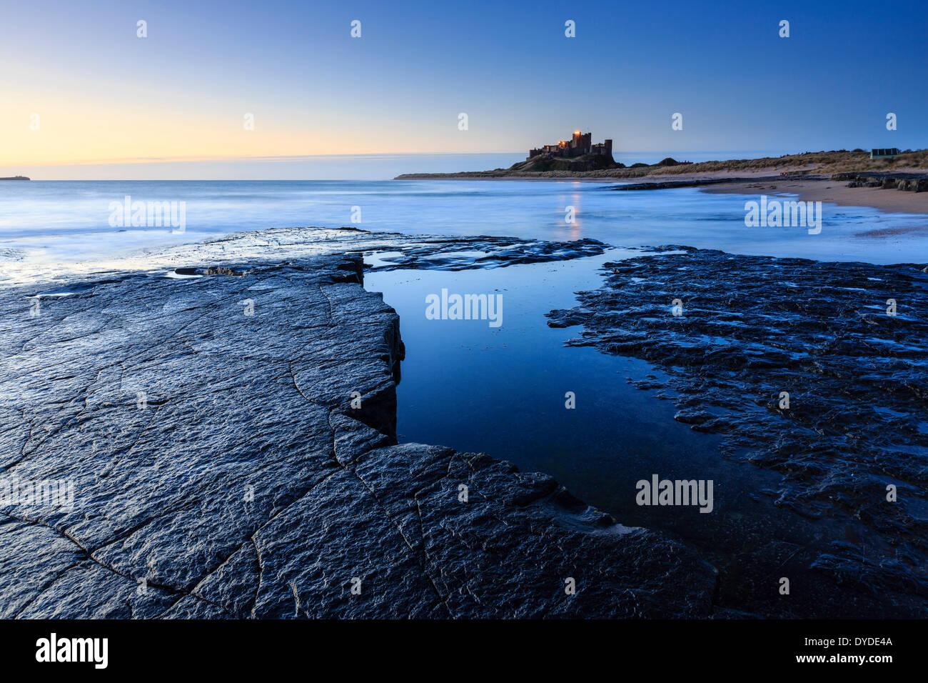 Guardando verso il castello di Bamburgh all'alba. Immagini Stock