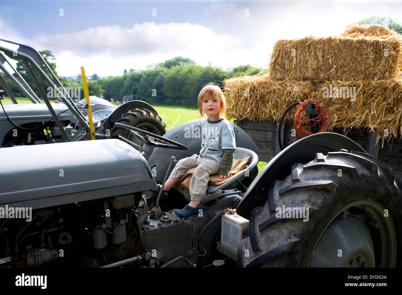 Un bimbo di 2 anni seduto su un trattore. Immagini Stock