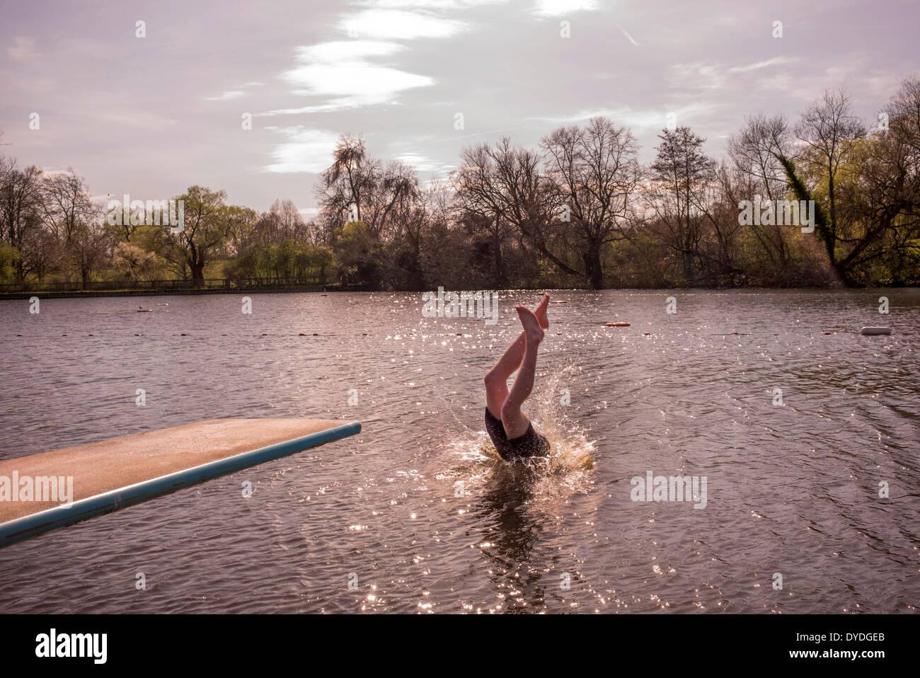 Un giovane uomo di nuoto in primavera acqua fresca stagni. Immagini Stock