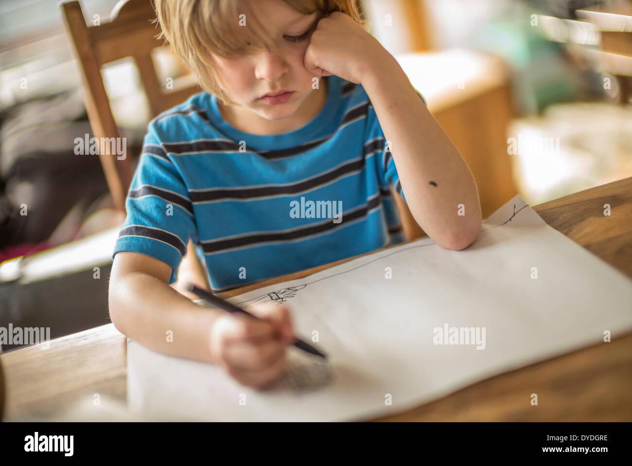 Sette anni di disegno del ragazzo al tavolo. Immagini Stock